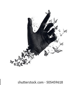 Life transformation concept image of butterflies flying out and around of black painted hand. Abstract symbol of freedom or dream, hope renewal and spirituality or human faith. Isolated. Monochrome