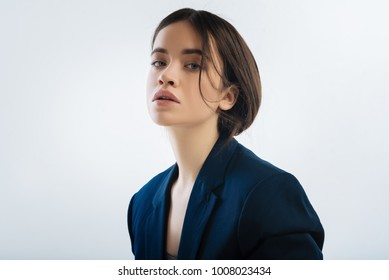 Life trap. Focused attractive good looking woman standing on the isolated background and gazing at the camera while wearing jacket