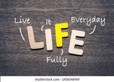 LIFE wooden alphabets on wood background with text acronym (Live It Fully Everyday)