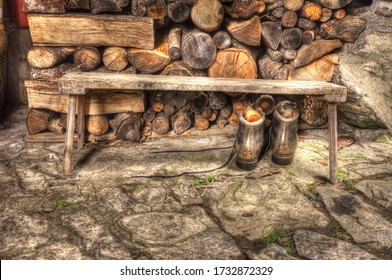 Life in the woods. A closeup of a pile of stored logs in a cabin beside a wooden bench and a pair of woodsman's boots