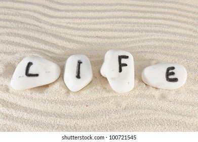Life word on group of stones with sand as background