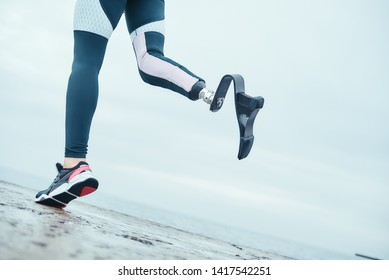 Life is in your hands. Cropped photo of disabled woman with bionic leg in sportswear is running on the beach in the morning.