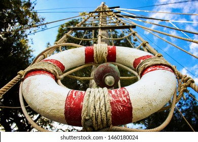Lifebelt on the wooden mast tied with cord or a rope view from the bottom