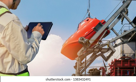 Lifeboat or rescue boat in shipyard, Worker discussing over tablet compute, under ship maintenance and check by inspector, surveyor, during crane lifting Safety lifeboat stern ship for Maintenance.