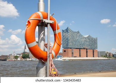 Lifebuoy at the jetty with background from the upper harbor in Hamburg