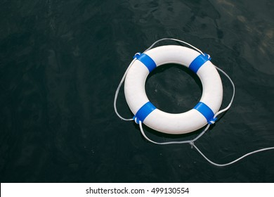 Lifebuoy, lifebelt on sea surface as safe, help, hope, protection, security concept background
