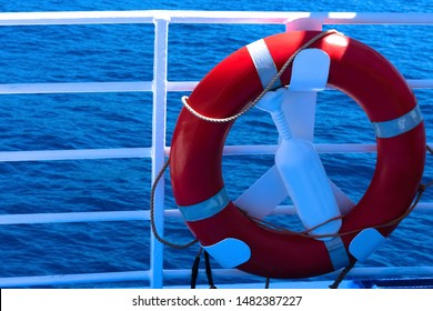 Lifebuoy on the boat. View at a red lifebuoy ring and Mediterranian sea