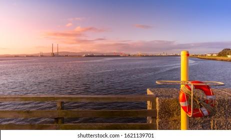 Lifebuoy on a bridge wall. Dublin port with crane and Poolbeg Power Plant in a distance. Amazing sunrise at Dublin bay, Ireland