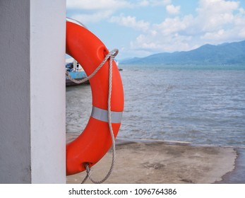 Lifebuoy on the pole of the building on the beach side of pier for thrown to a person in the water to rescue or provide buoyancy and prevent drowning, Lifesaver, Kisby ring or Perry buoy.