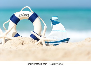 Lifebuoy on sand beach background with starfish and fishing boat, copy space. Summer Concept