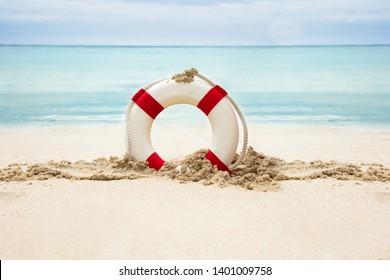 Lifebuoy On The Sandy Beach In Front Of Idyllic Sea
