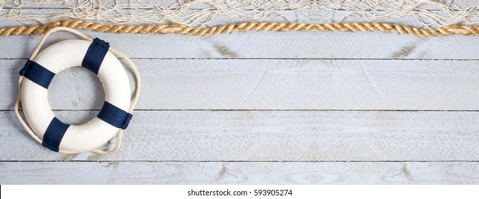 Lifebuoy on wooden background texture with rope and fishing net, copy space for individual text
