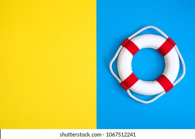 Lifebuoy on a yellow and blue background with blank space for text. Top view travel or vacation concept. Summer background. Flat lay photo, top view