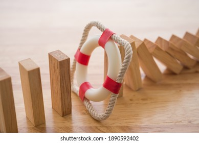 Lifebuoy stop wood block fall domino effect on office wooden table background. Life, health and property insurance business concept. Insurance is risk control management.