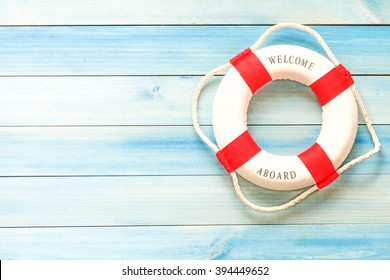 Lifebuoy with Welcome aboard phrase on wooden background