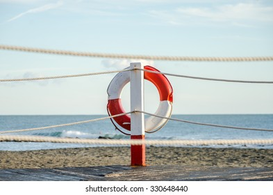 Lifebuoy white and red ropes hanging near the pier on the waterfront in Italy against the sky and the sea