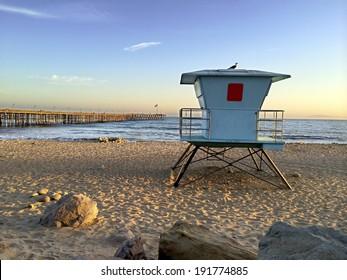 Lifeguard booth towering above sand near historic wooden pier, San Buenaventura, Southern California