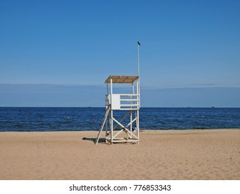 Lifeguard chair on beach with baltic sea and clear blue sky background