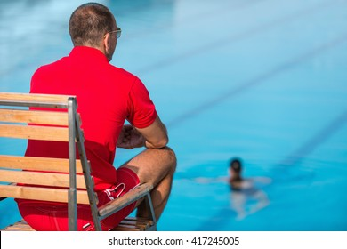 Lifeguard in chair, overlooking swimming pool