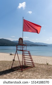 Lifeguard chair with red flag waving. No swimming concept. Beach of Galicia, Spain