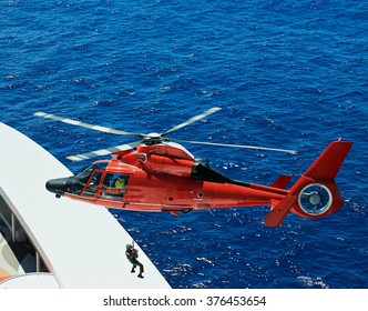 lifeguard descend from helicopter on ship at blue sea