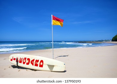 Lifeguard flag and board against blue sky