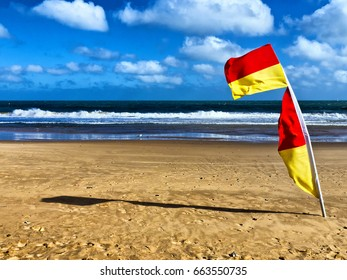 Lifeguard flag; red and yellow bathing flag flying on sandy beach; surf in background