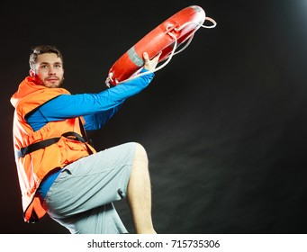 Lifeguard in life vest jacket throwing ring buoy lifebuoy. Man supervising swimming pool water on black. Accident prevention.