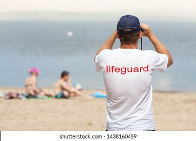 Lifeguard on the beach looking through binoculars. Safety while swimming.