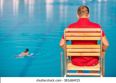 Lifeguard on duty, sitting in lifeguard chair, overlooking pool. Polarizing filter