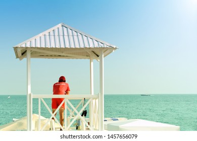 lifeguard on sea beach in watch tower on rescue duty against blue ocean water background back view of person in red t-shirt and swimming shorts with lifeguard label guarding sea shore outdoor activity
