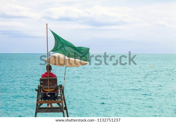 Lifeguard on the seafront. Guarded beach, watchtower with a green flag.