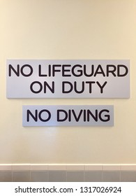 """A """"No Lifeguard On Duty"""" and """"No Diving"""" sign on the wall at a swimming pool."""