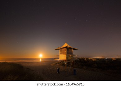 Lifeguard patrol tower at night with Moon on horizon, The Spit, Gold Coast Australia