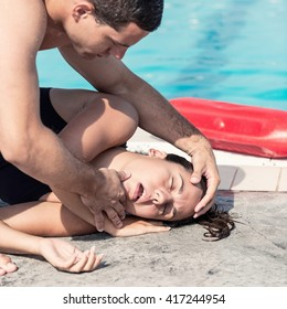 Lifeguard performing medical procedure with swimming pool accident victim