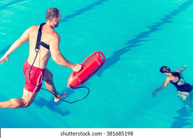 Lifeguard rescue course - lifeguard jumping towards victim. Toned image