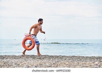 Lifeguard running with lifebuoy. Sea background.
