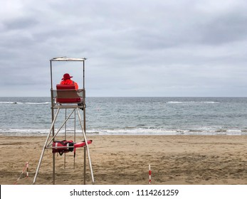 Lifeguard sheltered at his tower on a cloudy day at the beach