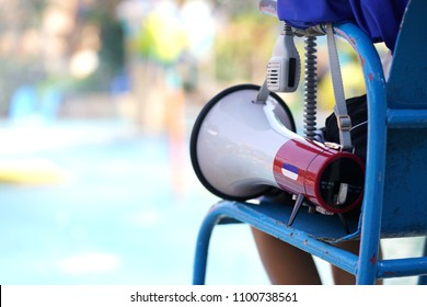 lifeguard sitting on chair with megaphone at poolside for guarding lives.