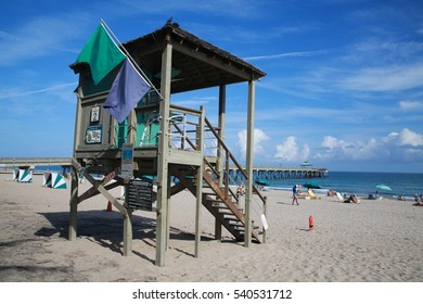 Lifeguard Station with Green Flags Surrounded by Orange Cones in the Sand with Deerfield Beach, Florida Pier in the Background, Sunny Afternoon with Scattered Clouds