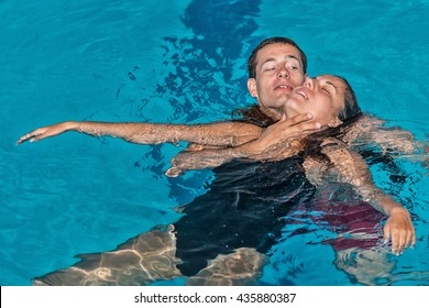 lifeguard swimming with victim keeping her head above water