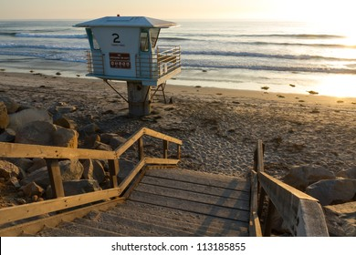 Lifeguard tower at bottom of stairs leading to beach with the glow of the summertime evening sun.