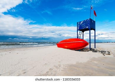 lifeguard tower and lifeboat on the beach - with blue cloudy sky in background