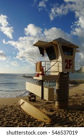 Lifeguard tower on beach with surfboard and clouds in Hawaii