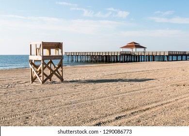 Lifeguard tower on an empty beach with the public viewing pier at Buckroe Beach in Hampton, Virginia.