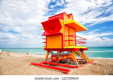 Lifeguard tower for rescue baywatch on south beach in Miami, USA. Red and yellow wooden house on sea shore on cloudy sky background. Summer vacation and resort. Public guarding and safety concept