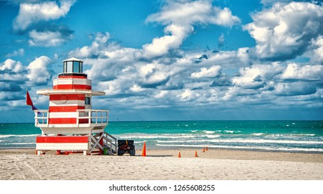 Lifeguard tower for rescue baywatch on south beach in Miami, USA. Red and white wooden house on sea shore on cloudy sky background. Summer vacation and resort. Public guarding and safety concept