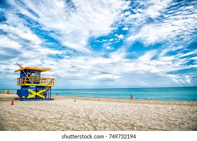 Lifeguard tower for rescue baywatch on south beach in Miami, USA. Red and blue wooden house on sea shore on cloudy sky background. Summer vacation and resort. Public guarding and safety concept