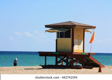 Lifeguard tower at sunny day at Florida Beach, red flag, no swimming, person walking on background