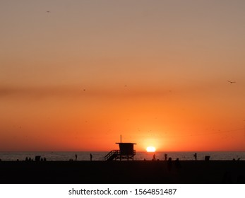 Lifeguard tower at sunset on Santa Monica beach, California. Sun dips into the ocean.